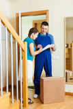Delivery man in uniform delivered a parcel to young  woman at ho Stock Photos