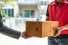 Delivery man uniform handing parcel box to recipient - courier royalty free stock photos