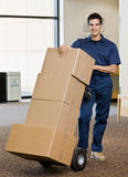 Delivery man in uniform pushing stack of boxes