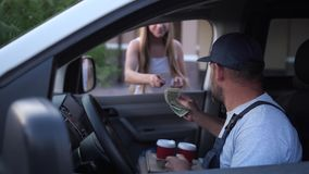 Female client taking coffee from delivery man. Delivery man in uniform sitting in van giving ordered cups of coffee drink to attractive woman customer. Blonde stock footage