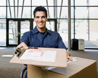 Delivery man in uniform with stack of boxes Royalty Free Stock Photos