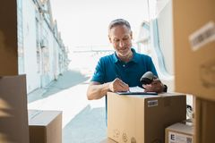 Delivery man updating checklist. Delivery man signing checklist and holding scanner in hand. Happy courier writing on clipboard and scanning barcode. Mature man Stock Images
