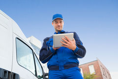 Delivery Man Using Digital Tablet By Truck Against Sky. Low angle view of delivery man using digital tablet by truck against sky Stock Image