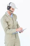 Delivery man using headphones while writing on clipboard Royalty Free Stock Photography