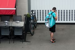 Delivery man waiting with smartphone near restaurant, deliveroo is a british delivery company in mountain bike royalty free stock photos