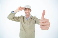 Delivery man wearing cap while gesturing thumbs up Stock Photos