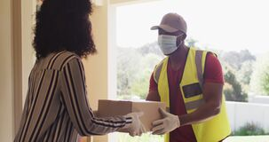 Delivery man wearing face mask delivering package to african american woman wearing face mask at hom