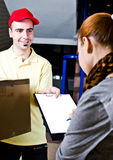 Delivery man at work. A handsome young courier delivering a package Royalty Free Stock Photo