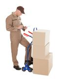 Delivery man writing on clipboard by cart and cardboard boxes Royalty Free Stock Images