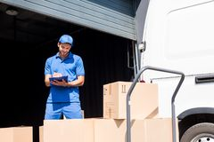 Delivery man with clipboard. Delivery man writing in clipboard next to warehouse Stock Photo