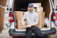 Delivery man writing on clipboard Royalty Free Stock Images