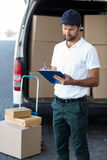 Delivery man writing on clipboard while standing next to his van Royalty Free Stock Photos