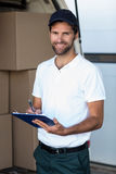 Delivery man writing on clipboard while standing next to his van Stock Images