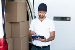Delivery man writing on clipboard while standing next to his van Stock Photo