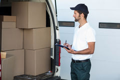 Delivery man writing on clipboard while standing next to his van Royalty Free Stock Photography