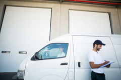 Delivery man writing on clipboard while standing next to his van Royalty Free Stock Photo