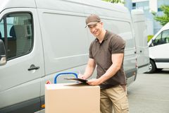Delivery Man Writing On Clipboard. Young Happy Delivery Man With Cardboard Boxes Writing On Clipboard Stock Photos