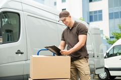 Delivery Man Writing On Clipboard Royalty Free Stock Photos