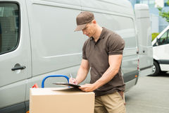 Delivery Man Writing On Clipboard. Young Happy Delivery Man With Cardboard Boxes Writing On Clipboard Stock Photo