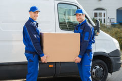 Delivery Men Carrying Cardboard Box Against Truck. Portrait of happy delivery men carrying cardboard box while standing against truck stock image