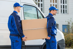 Delivery Men Carrying Cardboard Box By Truck. Side view of young delivery men carrying cardboard box while walking by truck stock photos