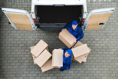 Delivery Men Carrying Cardboard Boxes Outside Truck Stock Image
