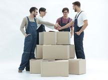 Cheerful movers leaning on stack of boxes isolated on white back. Delivery men carrying stack of boxes. Isolated on white Royalty Free Stock Images