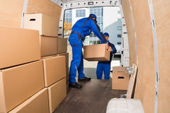 Delivery Men Loading Cardboard Boxes. Young delivery men loading cardboard boxes in truck Stock Photos