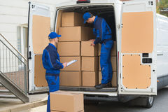 Delivery Men Unloading Boxes. Delivery men unloading cardboard boxes from truck while colleague writing on clipboard Stock Images