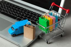 Delivery of orders from the online store. Shopping bags in shopping cart on laptop keyboard and courier delivery truck royalty free stock photos