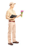 Delivery person holding a clipboard and bunch of flowers Royalty Free Stock Photo