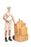 Delivery person holding a clipboard and hand truck. Full length portrait of a delivery person holding a clipboard and hand truck  on white background Royalty Free Stock Images