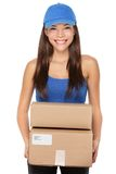Delivery person holding packages. Wearing blue cap. Woman courier smiling happy isolated on white background. Beautiful young mixed race Caucasian / Chinese royalty free stock image