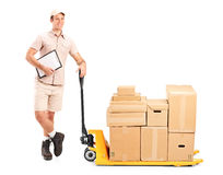 Delivery person next to fork pallet truck Royalty Free Stock Photos