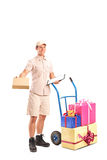 Delivery person posing next to a hand truck. Full length portrait of a delivery person posing next to a hand truck with presents  on white background Royalty Free Stock Photos