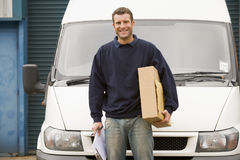 Delivery person standing with parcel Royalty Free Stock Images
