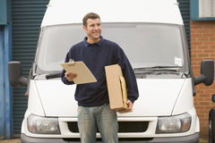 Delivery person standing with parcel and clipboard. Infront of his van Stock Photos