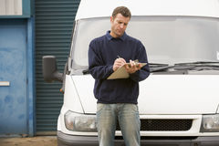 Delivery person standing with van writing. On clipboard Royalty Free Stock Photos