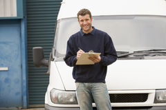 Delivery person standing with van writing. On clipboard Stock Image