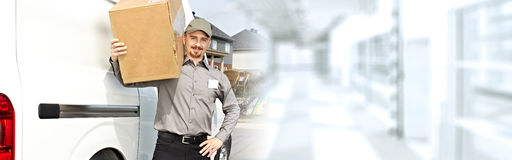 Delivery postman with a box Stock Images