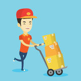Delivery postman with cardboard boxes on trolley. Royalty Free Stock Photography