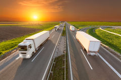 Delivery reefer transport trucks on the empty highway at sunset