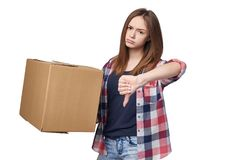 Delivery, relocation and unpacking. Discontent young woman holding cardboard box and gesturing thumb down, isolated on white background Stock Photos