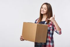 Delivery, relocation and unpacking. Smiling young woman holding cardboard box showing call me gesture. Call center and customer support service concept Stock Photos