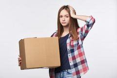 Delivery, relocation and unpacking problems. Discontent young woman holding cardboard box with hand on head Royalty Free Stock Photos