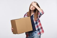 Delivery, relocation and unpacking problems. Discontent young woman holding cardboard box with hand on head Royalty Free Stock Photo