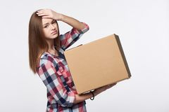 Delivery, relocation and unpacking problems. Discontent young woman holding cardboard box with hand on head Stock Photography