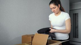 Delivery, relocation and unpacking. young woman packs things in cardboard box royalty free stock image