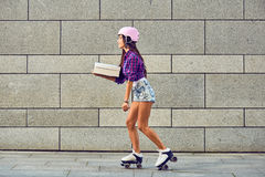 Delivery on roller skates by beautiful girl in helmet Royalty Free Stock Photography