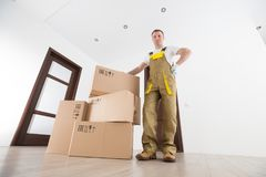 Delivery service background. Delivery man with big boxes in empty apartment royalty free stock photography